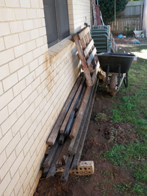 Conditions conducive to attracting termites: wood stacked against external walls.