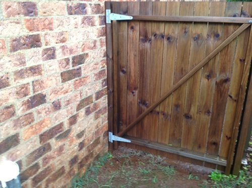 Conditions conducive to attracting termites: gate posts secured to external wall.